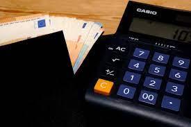 calcolatrice con mazzetta di euro affianco